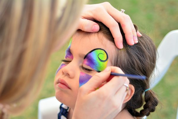 45832358 - little girl getting her face painted like a butterfly.